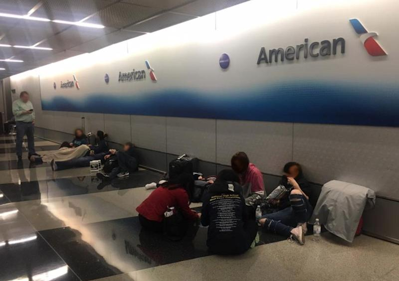 Nine high school students and 11 adults were forced to sleep on the floor at baggage claim after American Airlines cancelled their flight home. (Photo: Facebook)