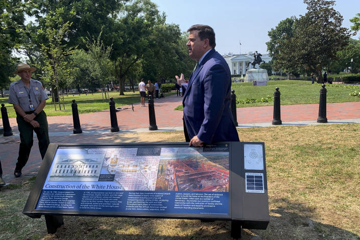 A new historical marker that addresses the construction of the White House by both enslaved people and paid laborers is displayed at the northern end of Lafayette Park on Wednesday, July 28, 2021, in Washington. The White House Historical Association on Wednesday unveiled three new historical markers at the northern end of Lafayette Park. (AP Photo/Ashraf Khalil)
