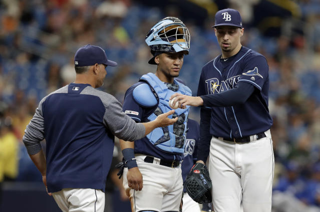 Tampa Bay Rays pitcher Blake Snell, right, hands the ball to manager Kevin Cash, left, as he is taken out of the game against the Kansas City Royals during the fourth inning of a baseball game Wednesday, April 24, 2019, in St. Petersburg, Fla. Looking on is Rays catcher Michael Perez. (AP Photo/Chris O'Meara)
