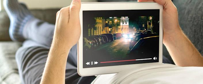 Man watching film on his tablet using Netflix or some other video streaming service