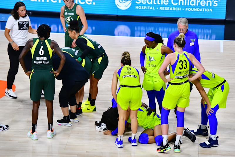 Teammates surround Sue Bird and Satou Sabally on the court.