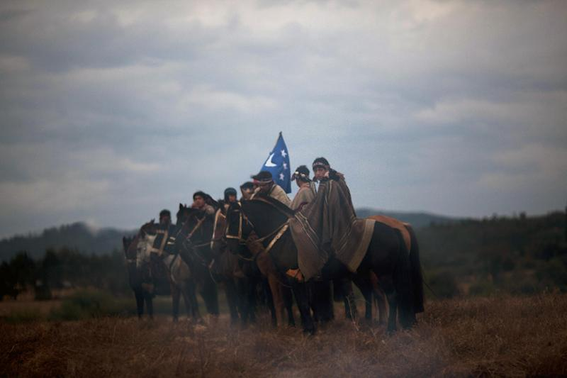 """In this Feb. 10, 2013 photo, Mapuche Indians gather for a """"Guillatun,"""" a spiritual ceremony to ask for the well-being of the clan and strengthen ties in the Temucuicui Autonomous community in Ercilla, Chile. """"We're not trying to kick anybody out,"""" said Aucan Huilcaman, a Mapuche leader. """"We're not asking for more roads or more seeds. We're asking for our own government because this is our land. It's not anti-Chilean, it's pro-Mapuche."""" (AP Photo/Rodrigo Abd)"""