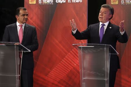 Colombia's President and presidential candidate Juan Manuel Santos gestures as presidential candidate Oscar Ivan Zuluaga looks on during a television debate in Bogota