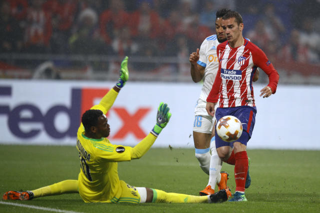 Atletico's Antoine Griezmann, right, scores 2-0 passing Marseille's goalkeeper Steve Mandanda, left, and Marseille's Jordan Amavi, rear, during the Europa League Final soccer match between Marseille and Atletico Madrid at the Stade de Lyon in Decines, outside Lyon, France, Wednesday, May 16, 2018. (AP Photo/Francois Mori)