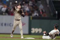 San Diego Padres second baseman Adam Frazier, left, throws to first base after forcing San Francisco Giants' Tommy La Stella, right, out at second base on a double play hit into by Buster Posey during the first inning of a baseball game in San Francisco, Wednesday, Sept. 15, 2021. (AP Photo/Jeff Chiu)