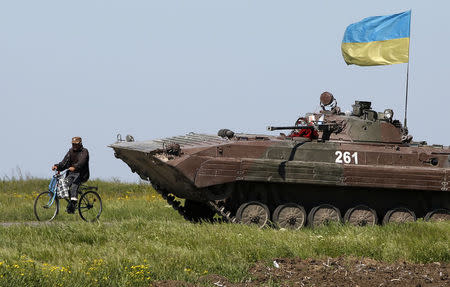 A man rides a bike past a Ukrainian armoured personnel carrier at a checkpoint in Mariupol, eastern Ukraine May 7, 2014. REUTERS/Marko Djurica