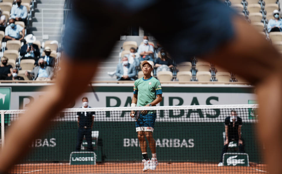 Japan's Kei Nishikori jumps to see where the ball lands as he plays against Russia's Karen Khachanov during their second round match on day four of the French Open tennis tournament at Roland Garros in Paris, France, Wednesday, June 2, 2021. (AP Photo/Thibault Camus)
