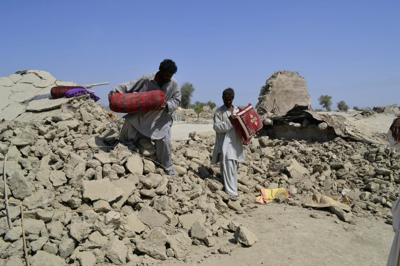 Survivors of an earthquake collect their belongings near the rubble of a mud house after it collapsed following the quake in the town of Awaran, southwestern Pakistani province of Baluchistan, September 25, 2013. The death toll from a powerful earthquake in southwest Pakistan rose to 327 on Wednesday after hundreds of mud houses collapsed on residents throughout the remote and thinly populated area, local officials said, REUTERS/Naseer Ahmed (PAKISTAN - Tags: DISASTER ENVIRONMENT)