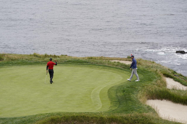 Tiger Woods, left, waves after birdie on the seventh hole and Marc Leishman, of Australia, looks on during the final round of the U.S. Open Championship golf tournament Sunday, June 16, 2019, in Pebble Beach, Calif. (AP Photo/David J. Phillip)