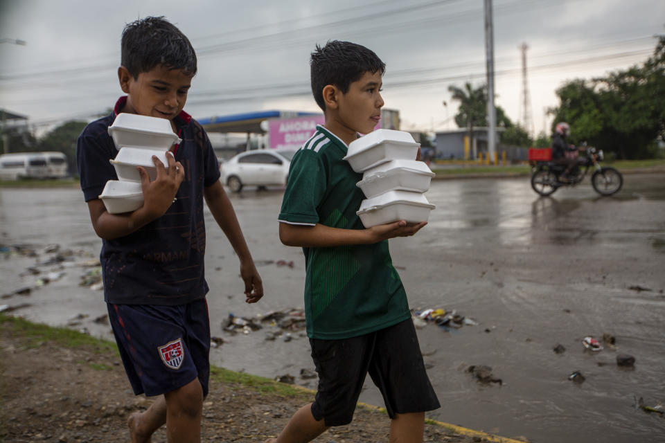 Youths carry donated hot meals back to their tents alongside a highway where they live with others after last year's hurricanes Eta and Iota left their family's homeless in San Pedro Sula, Honduras, Tuesday, Jan. 12, 2021. The World Food Program says the number of Hondurans facing food insecurity is 3 million, six times higher than before. (AP Photo/Moises Castillo)