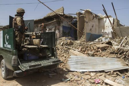 Pakistani soldiers look at a house which was destroyed during a military operation against Taliban militants, in the of town of Miranshah