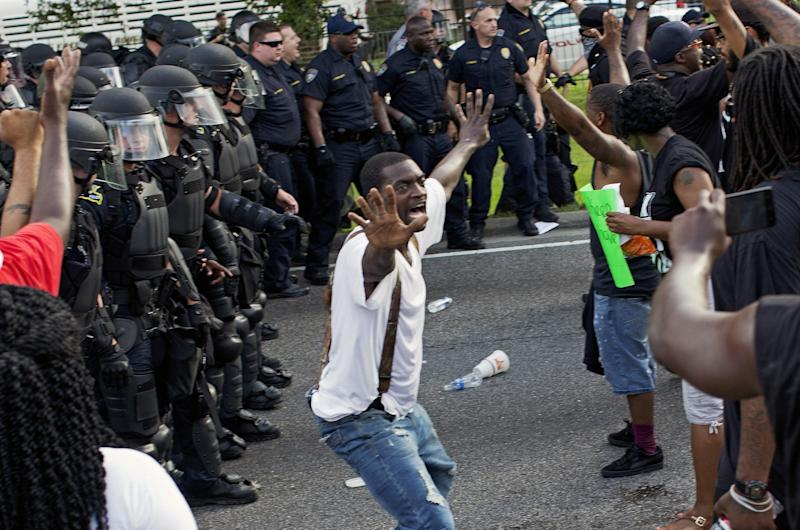 A man attempts to stop protesters from engaging with police in riot gear in front of the Baton Rouge Police Department headquarters after police attempted to clear the street in Baton Rouge, La., Saturday, July 9, 2016. Several protesters were arrested. (AP Photo/Max Becherer)
