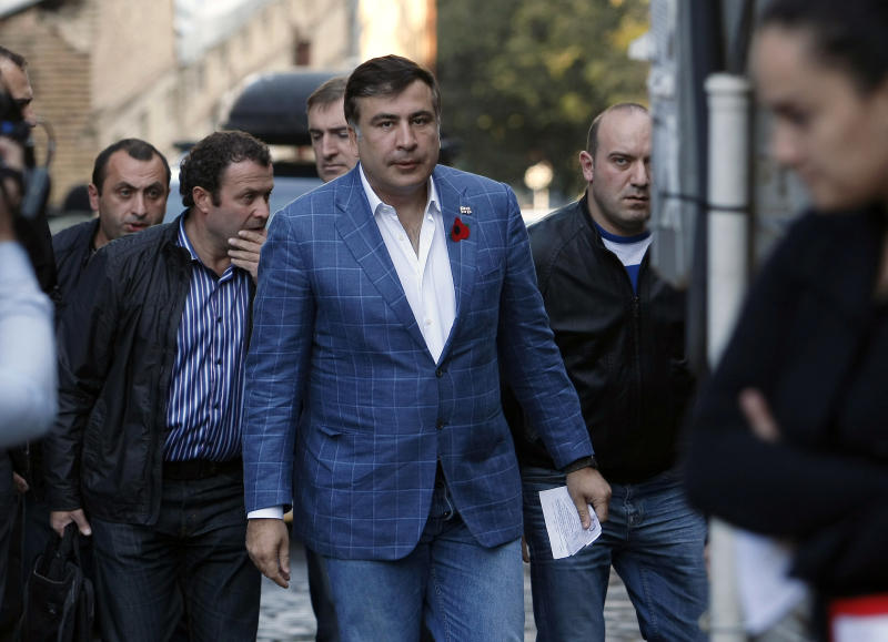 Surrounded by bodyguards, outgoing Georgian President Mikhail Saakashvili walks to cast his ballot at a polling staiton during the presidential election in Tbilisi, Georgia, Sunday, Oct. 27, 2013. Georgians voted Sunday for a president to succeed Mikhail Saakashvili, who during nearly a decade in power has turned this former Soviet republic into a fledgling democracy and a staunch U.S. ally. (AP Photo/ Shakh Aivazov)