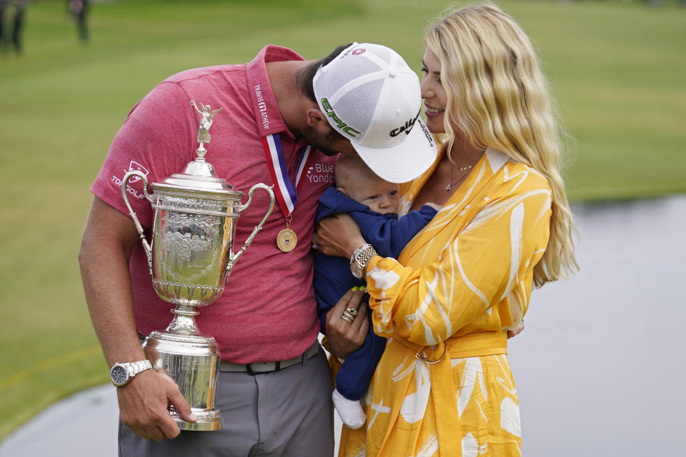 Jon Rahm, of Spain, holds the champions trophy for photographers as he stands with his wife, Kelley Rahm and kisses their child, Kepa Rahm, 11 months, after the final round of the U.S. Open Golf Championship, Sunday, June 20, 2021, at Torrey Pines Golf Course in San Diego. (AP Photo/Marcio Jose Sanchez)