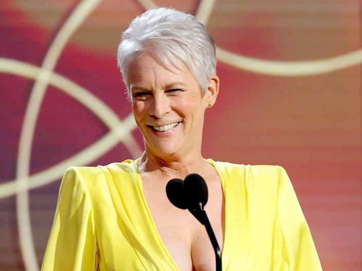A woman (actress Jamie Lee Curtis) with short gray hair, wearing a yellow evening gown, stands in front of a black microphone.