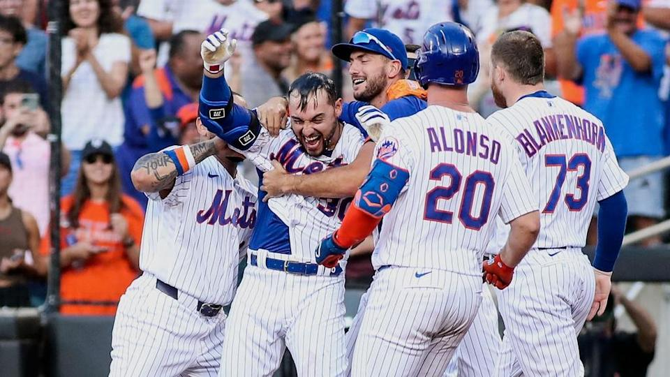 Jun 26, 2021; New York City, New York, USA; New York Mets right fielder Michael Conforto (30) is mobbed by teammates after hitting a sacrifice fly to defeat the Philadelphia Phillies at Citi Field.