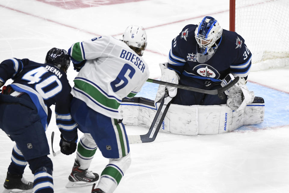 Winnipeg Jets goaltender Laurent Brossoit (30) makes a save on Vancouver Canucks' Brock Boeser (6) during the third period of an NHL game in Winnipeg, Manitoba, Monday, May 10, 2021. (Fred Greenslade/The Canadian Press via AP)