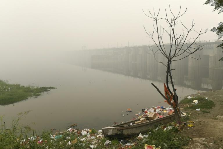 A boat is seen amidst heavy smog conditions surrounded by rubbish near a bridge along the Yamuna River in New Delhi (AFP Photo/Sajjad HUSSAIN)
