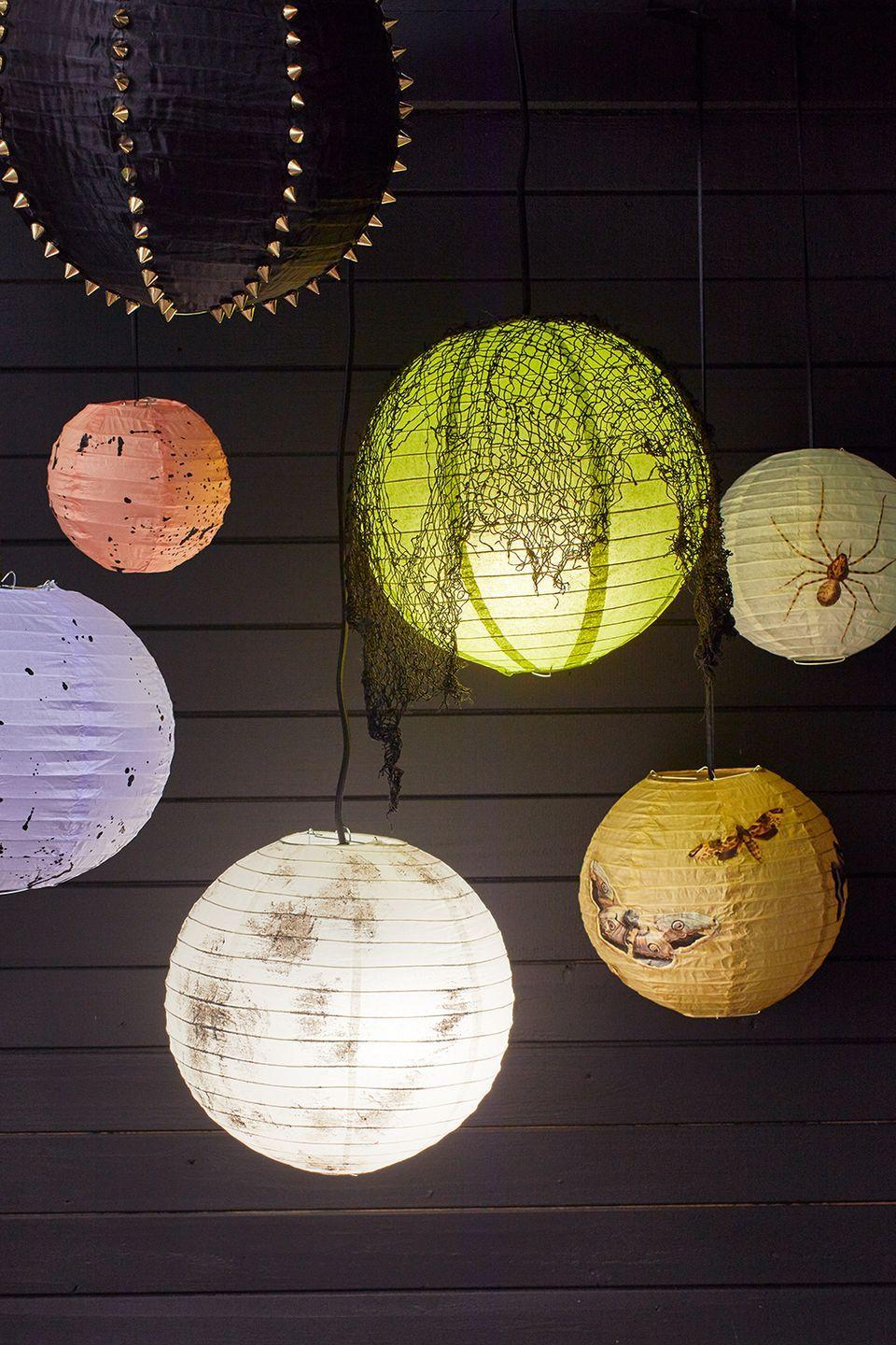 """<p>Simple paper lanterns are easily transformed with clip art, paint, studs and gauze. They look even more eerie in the dark!</p><p><em><a href=""""https://www.goodhousekeeping.com/home/craft-ideas/a34329004/diy-halloween-lantern-tutorial/"""" rel=""""nofollow noopener"""" target=""""_blank"""" data-ylk=""""slk:Get the tutorial »"""" class=""""link rapid-noclick-resp"""">Get the tutorial »</a></em></p>"""