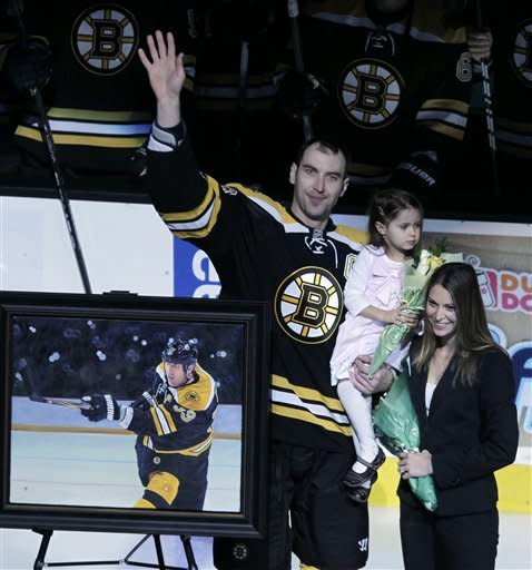 Boston Bruins defenseman Zdeno Chara, of Slovakia, waves alongside his wife, Tatiana and daughter Elliz Victoria as he is honored for having played in 1,000 NHL hockey games during a ceremony prior to an NHL hockey game against the Tampa Bay Lightning, Tuesday, March 27, 2012, in Boston. (AP Photo/Elise Amendola)