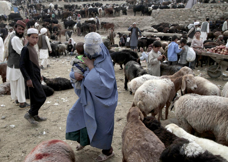"An Afghan woman begs for money at a livestock market set up for the upcoming Muslim holiday of Eid al-Adha, or ""feast of sacrifice,"" on the outskirts of Kabul, Afghanistan, Sunday, Oct. 13, 2013. Muslims all over the world celebrate the three-day Eid al-Adha, by sacrificing sheep, goats, and cows to commemorate the Prophet Abraham's readiness to sacrifice his son, Ismail, on God's command. (AP Photo/Rahmat Gul)"