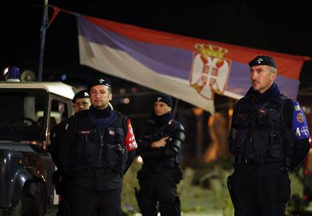 Italian Carabinieri, who are members of NATO's KFOR, stand in front of a Serbian national flag as they secure the main bridge in the northern part of Mitrovica