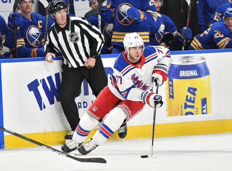 Tony DeAngelo skates near the bench with referee behind him