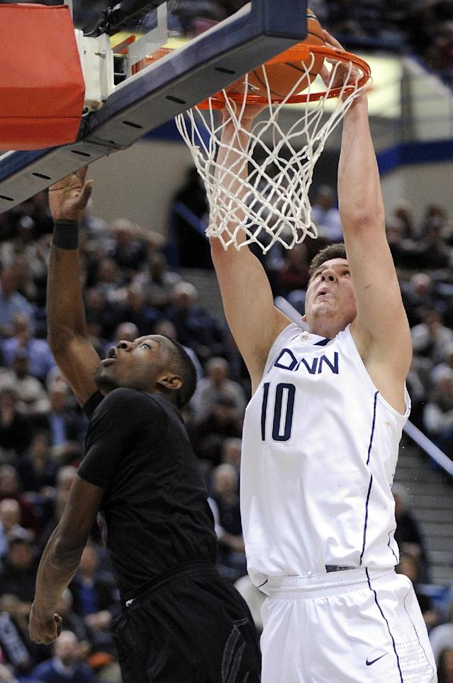 Connecticut's Tyler Olander, right, scores over Cincinnati's Justin Jackson during the second half of Connecticut's 73-66 overtime victory in an NCAA college basketball game in Hartford, Conn., Thursday, Feb. 21, 2013. (AP Photo/Fred Beckham)