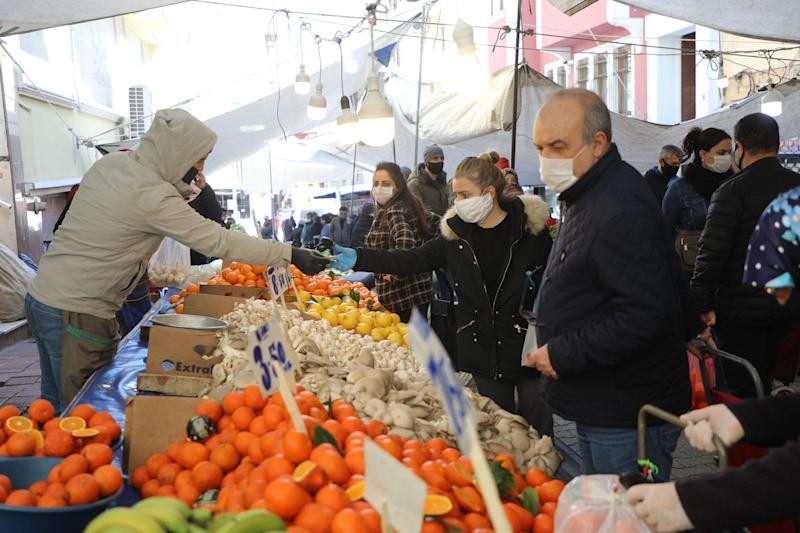 People put masks on their faces and shop their needs from the popular market on April 8 in Istanbul.