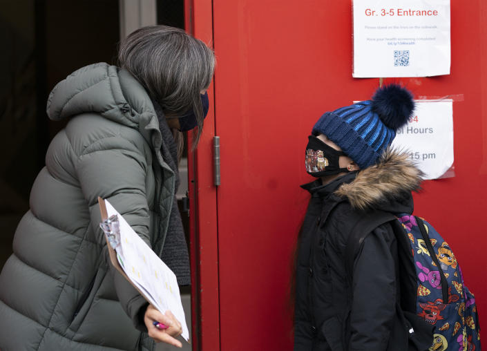 A school administrator, left, asks a student if his parents have completed a form granting permission for random COVID-19 testing as he arrives at P.S. 134 Henrietta Szold Elementary School, Monday, Dec. 7, 2020, in New York. Public schools reopened for in-school learning Monday after being closed since mid-November. (AP Photo/Mark Lennihan)