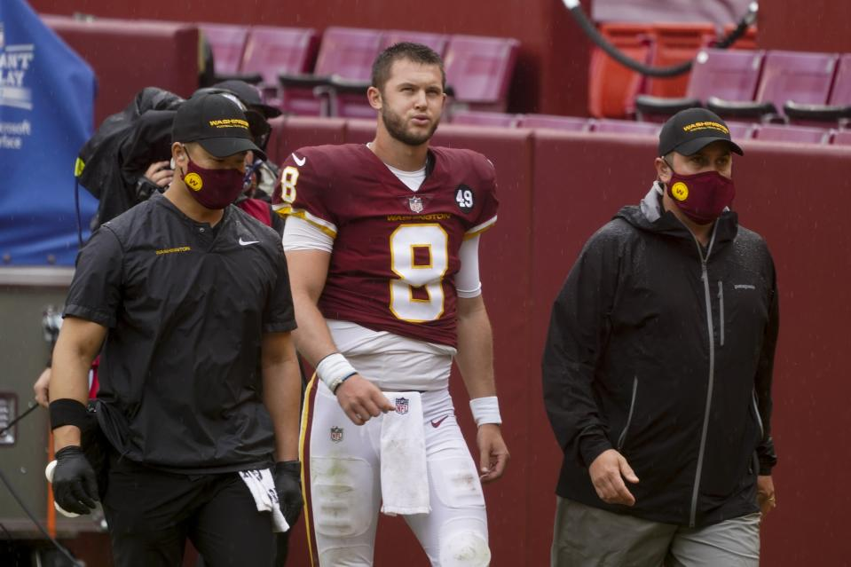 Kyle Allen walks with Washington Football Team trainers on the sideline without his helmet.