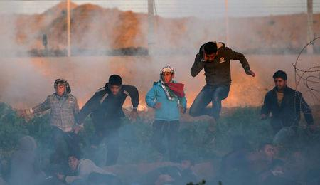 Palestinians run for cover from Israeli gunfire and tear gas during a protest at the Israel-Gaza border fence, in the southern Gaza Strip