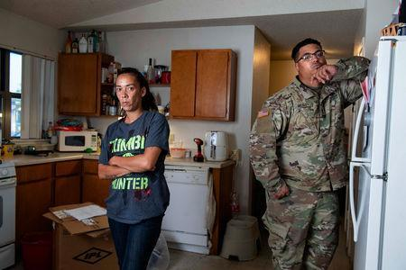 FILE PHOTO: Leanne Bell, 39, and her husband, Spc. Tevin Mosley, 26, who say they began suffering breathing issues, depression, and rashes, they attribute to a mold infestation, since moving into the army base housing allocated to their family in Fort Hood 3 years ago pose in the kitchen of their house in Fort Hood, Texas, U.S. May 16, 2019. Over the course of their stay they contacted housing maintenance repeatedly, submitting between 2 to 3 dozen work orders related to mold, HVAC, and air issue quality concerns. In March, the home was quarantined and the family had to be relocated until repairs could be completed. REUTERS/Amanda Voisard