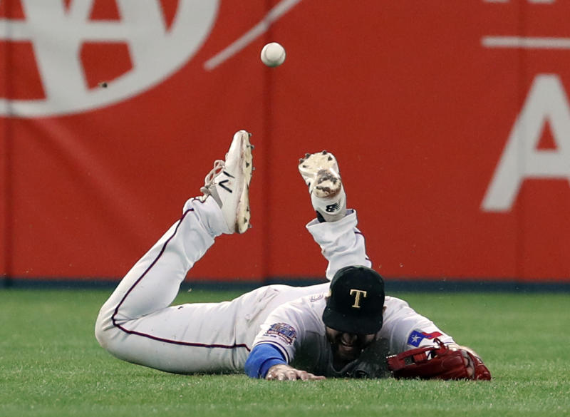 Texas Rangers center fielder Joey Gallo hits the ground hard while chasing a double by St. Louis Cardinals' Yadier Molina during the eighth inning of a baseball game in Arlington, Texas, Saturday, May 18, 2019. (AP Photo/Tony Gutierrez)
