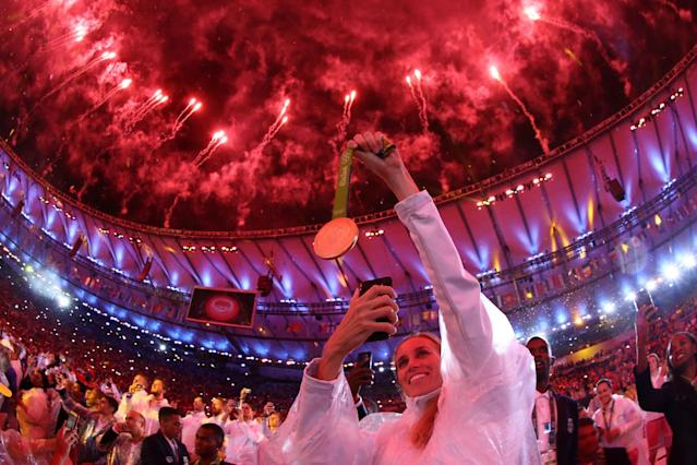 <p>An athlete takes a photo of their medal as fireworks explode near the conclusion of the Closing Ceremony on Day 16 of the Rio 2016 Olympic Games at Maracana Stadium on August 21, 2016 in Rio de Janeiro, Brazil. (Photo by Ezra Shaw/Getty Images) </p>