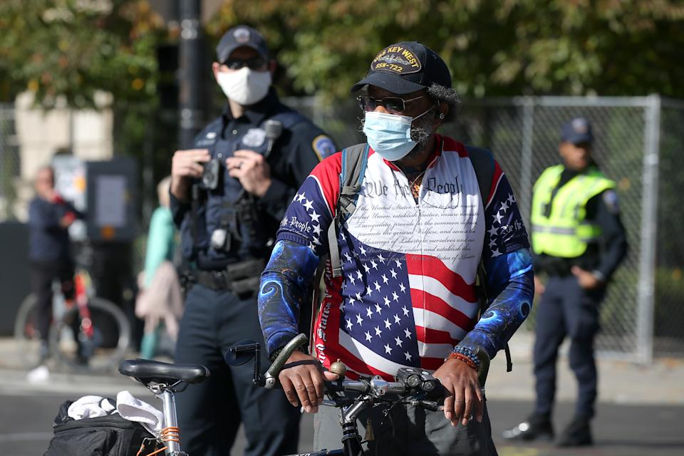 WASHINGTON D.C., UNITED STATES - NOVEMBER 5, 2020: A local man and polics officers in face masks at Black Lives Matter Plaza during a protest at the crossing of I Street NW and 16th Street NW. On November 3, 2020, Americans voted to elected a president and vice president, 35 Senators, all 435 members of the House of Representatives, 13 governors of 11 states and two US territories, as well as state and local government officials. Running for president are incumbent Republican President Trump and Democratic Party nominee Biden. Yegor Aleyev/TASS (Photo by Yegor Aleyev\TASS via Getty Images)