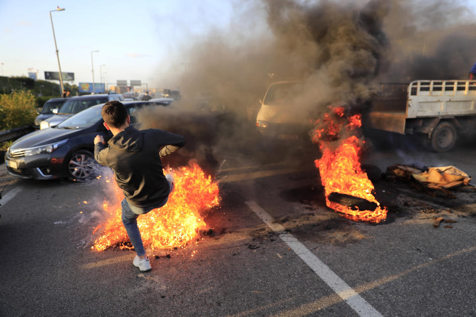 A protester kicks a burning tire that he set on fire to block a highway that links to the Beirut's international airport, during a protest against against the economic and financial crisis, in Beirut, Lebanon, Tuesday, March 2, 2021. The Lebanese pound has hit a record low against the dollar on the black market as the country's political crisis deepens and foreign currency reserves dwindle further. (AP Photo/Hussein Malla)