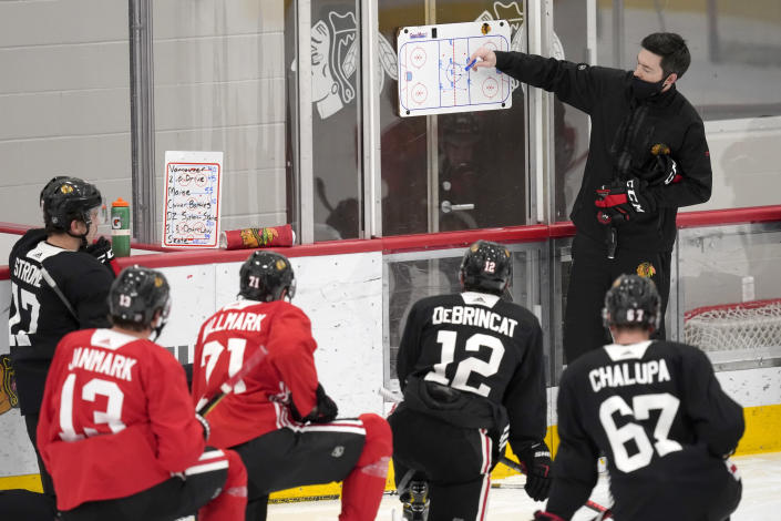 Chicago Blackhawks head coach Jeremy Colliton sets up a drill during an NHL hockey training camp practice Monday, Jan. 4, 2021, in Chicago. (AP Photo/Charles Rex Arbogast)