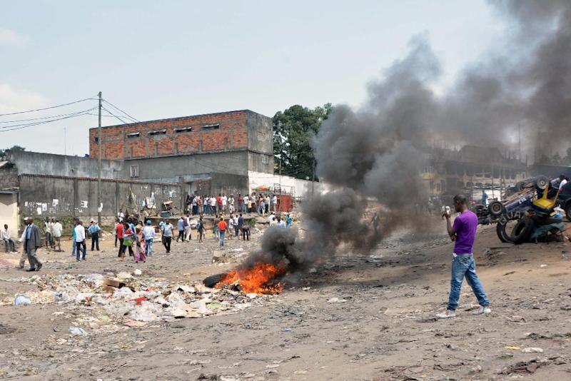 Protesters stand next to tyres set on fire on January 20, 2015 in Kinshasa, during a protest against moves to allow Democratic Republic of Congo's president to extend his hold on power (AFP Photo/Papy Mulongo)