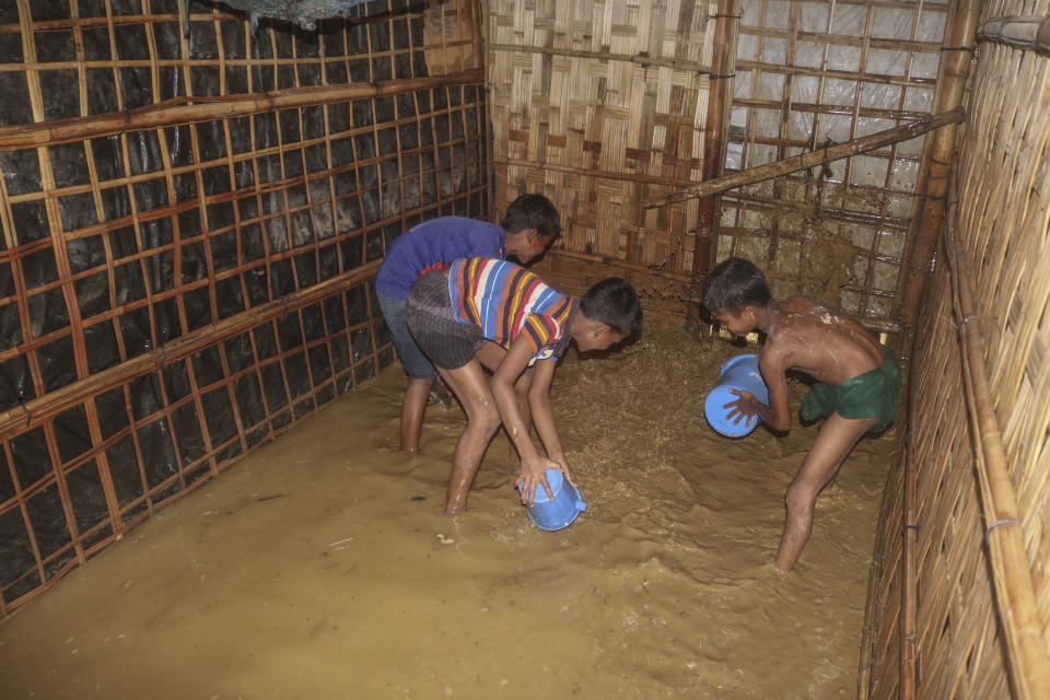 Rohingya refugee children try to pour away flood water from their homes at the Rohingya refugee camp in Kutupalong, Bangladesh, Wednesday, July 28, 2021. Days of heavy rains have brought thousands of shelters in various Rohingya refugee camps in Southern Bangladesh under water, rendering thousands of refugees homeless. (AP Photo/ Shafiqur Rahman)
