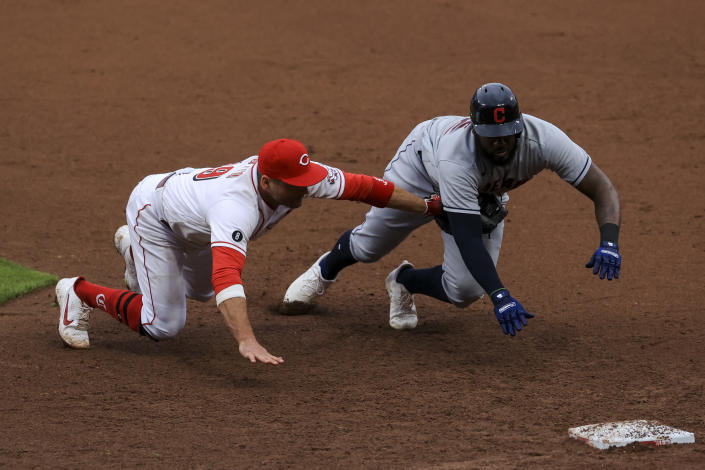 Cincinnati Reds' Joey Votto, left, dives and tags out Cleveland Indians' Franmil Reyes, right, for a triple play during the seventh inning of a baseball game in Cincinnati, Saturday, April 17, 2021. Indians' Josh Naylor lined out to Reds' Joey Votto to start the triple play. (AP Photo/Aaron Doster)