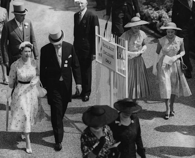Queen Elizabeth II and Princess Margaret, far right, walking into the paddock at the Royal Ascot race meeting in 1955. (PA Images)