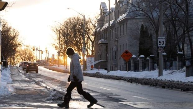 A person crosses St. Patrick Street near the ByWard Market in Ottawa. On Monday, Ottawa health officials reported 59 new cases of COVID-19 and one more death.