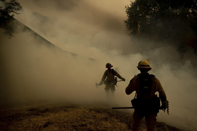 <p>A firefighter walks through smoke while fighting to save Olof Cellars winery in Lakeport, Calif., Monday, July 30, 2018. A pair of wildfires that prompted evacuation orders for nearly 20,000 people barreled Monday toward small lake towns in Northern California, and authorities faced questions about how quickly they warned residents about the wildfires. (Photo: Noah Berger/AP) </p>