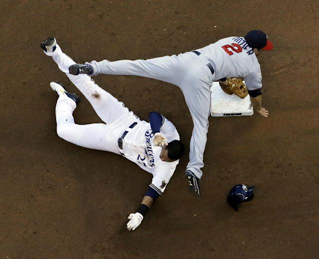 Minnesota Twins' Brian Dozier (2) leaps over Milwaukee Brewers' Carlos Gomez (27) at second to turn a double play on a ball hit by Khris Davis during the fourth inning of a baseball game, Monday, June 2, 2014, in Milwaukee. (AP Photo/Morry Gash)