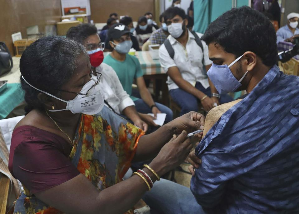 A health worker administers the Covishield, Serum Institute of India's version of the AstraZeneca vaccine, during a special vaccination drive for students traveling overseas, in Hyderabad, India, Friday, June 11, 2021. (AP Photo/Mahesh Kumar A.)