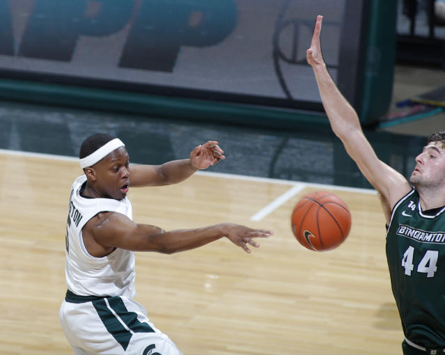 Michigan State's Cassius Winston, left, passes the ball as Binghamton's Yarden Willis defends during the first half of an NCAA college basketball game Sunday, Nov. 10, 2019, in East Lansing, Mich. Michigan State won 100-47. (AP Photo/Al Goldis)