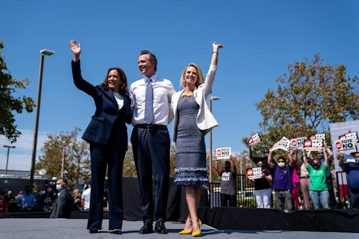 SAN LEANDRO, CA - SEPTEMBER 08: Vice President Kamala Harris, California Governor Gavin Newsroom and First Lady of California Jennifer Seibel-Newsom wave at a rally against the upcoming gubernatorial recall election at the IBEW-NECA Joint Apprenticeship Training Center on Wednesday, Sept. 8, 2021 in San Leandro, CA. The recall election, which will be held on September 14, 2021, asks voters to respond two questions: whether Newsom, a Democrat, should be recalled from the Office of Governor, and who would succeed Newsom should he be recalled. (Kent Nishimura / Los Angeles Times)