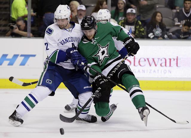 Vancouver Canucks defenseman Dan Hamhuis (2) strips the puck away from Dallas Stars center Tyler Seguin (91) during the first period of an NHL hockey game, Thursday, Dec. 19, 2013, in Dallas. (AP Photo/Tony Gutierrez)