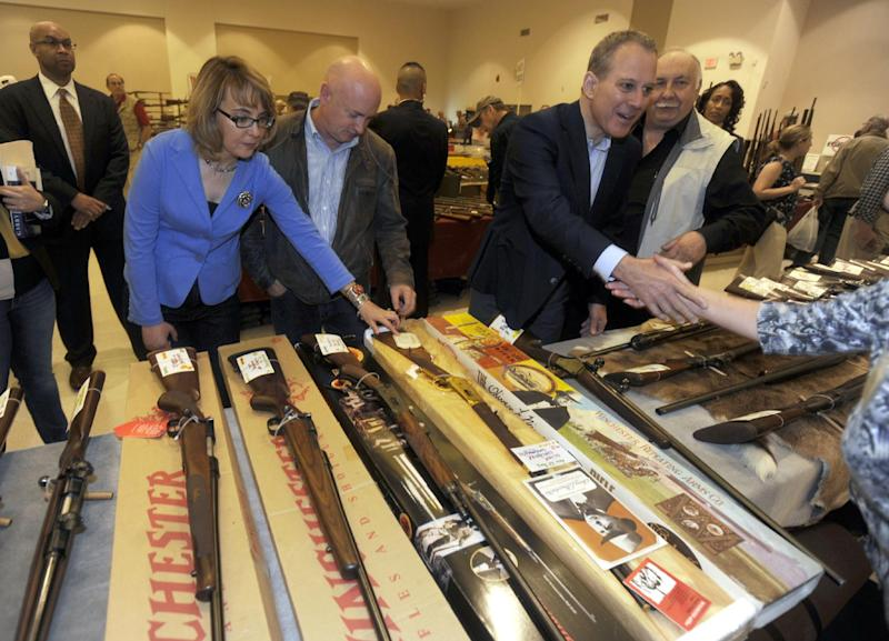 New York Attorney General Eric Schneiderman, right, former Arizona congresswoman Gabrielle Giffords, left, and her husband Mark Kelly, center, tour the New EastCoast Arms Collectors Associates arms fair in Saratoga Springs, N.Y. on Sunday, Oct. 13, 2013. (AP Photo/Tim Roske, Pool)